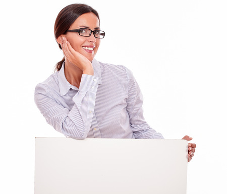 tied down: Satisfied brunette businesswoman with copy space, smiling and looking at the camera, wearing her straight hair tied back and a button down shirt, holding a placard on a white background Stock Photo