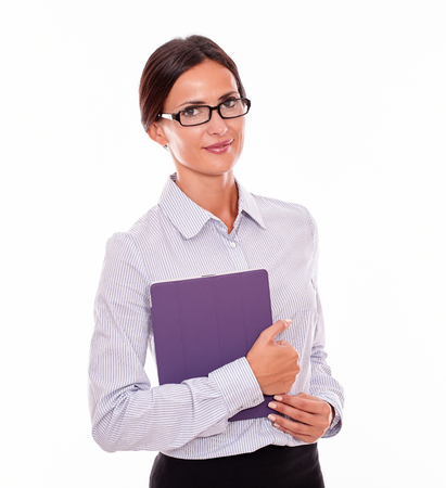 back straight: Smiling brunette businesswoman with glasses carrying a tablet, wearing her straight hair tied back and a button down shirt, looking at the camera, on a white background