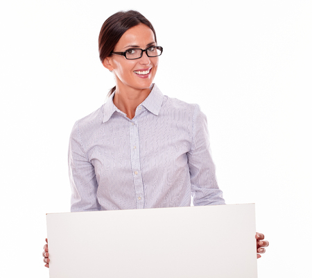 button down shirt: Smiling brunette businesswoman, wearing her straight hair tied back and a button down shirt, holding a blank placard in front of her with both hands on a white background Stock Photo
