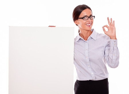 tied down: Impressed brunette businesswoman looking at the camera, holding a placard smiling, wearing her straight hair tied back and a button down shirt, with a gesture of her left hand a perfect sign Stock Photo