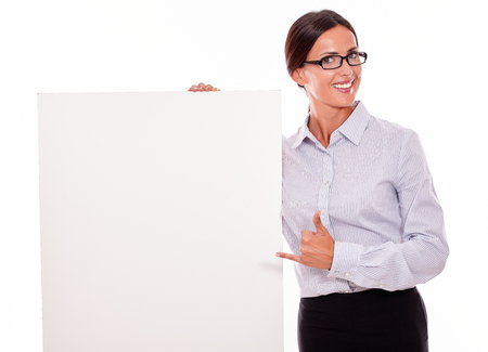 tied down: Happy brunette businesswoman looking at the camera, holding a placard with her toothy smile, wearing her straight hair tied back and a button down shirt, with a thumb up gesture, pointing at placard Stock Photo