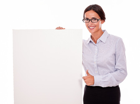 button down shirt: Happy smiling brunette businesswoman with glasses looking at the camera, holding a placard with her toothy smile, wearing her straight hair tied back and a button down shirt, with a thumb up gesture
