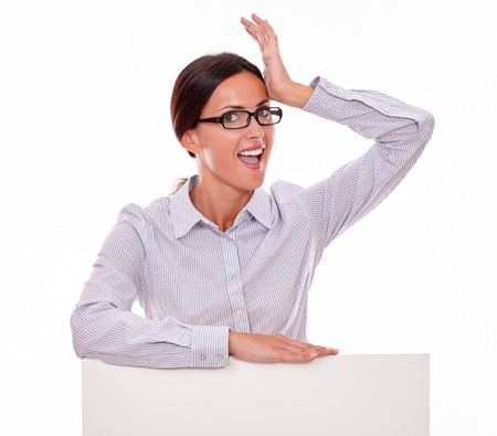 back straight: Excited brunette businesswoman gesturing with her left hand on her forehead, wearing her straight hair back looking at the camera with her mouth open in surprise on white background
