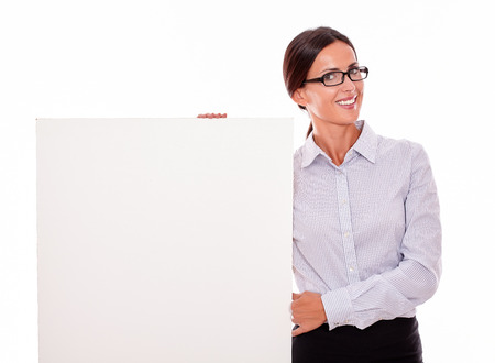 Happy brunette businesswoman with glasses looking at the camera, smiling while holding a placard, wearing her straight hair tied back and a button down shirt on a white background
