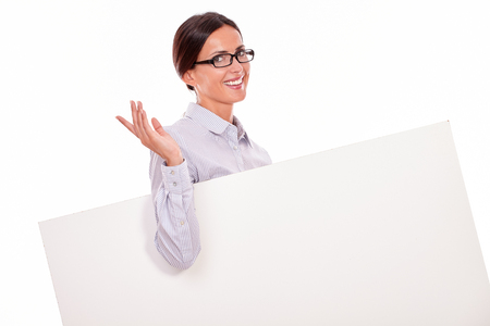 back straight: Happy, smiling brunette businesswoman looking at the camera while carrying a blank placard, wearing her straight hair tied back and a button down shirt on a white background
