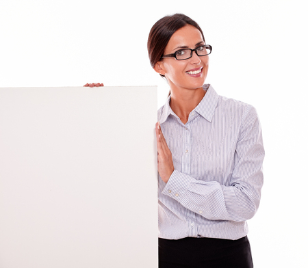 hair tied back: Happy, smiling brunette businesswoman looking at the camera while showing a blank placard, wearing her straight hair tied back and a button down shirt on a white background Stock Photo
