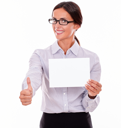 button down shirt: Satisfied brunette businesswoman, wearing her hair tied back and a button down shirt, holding a blank signboard with one hand and a thumb up gesture with her right hand on a white background