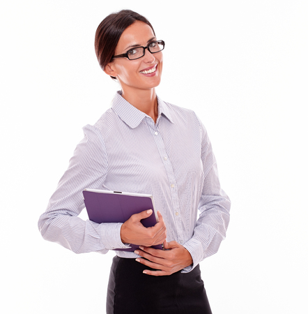 button down shirt: Smiling brunette businesswoman with glasses carrying a tablet, wearing her straight hair tied back and a button down shirt, looking at the camera on a white background