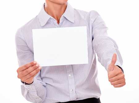 button down shirt: Satisfied businesswoman with a button down shirt, holding a blank signboard with one hand and a thumb up gesture with her left hand on a white background Stock Photo