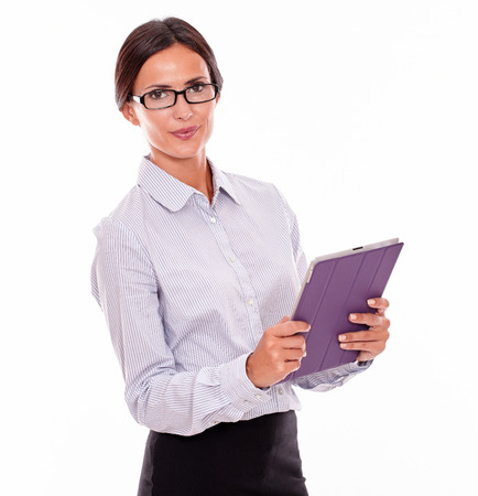button down shirt: Smiling brunette businesswoman with glasses carrying a tablet, wearing her straight hair tied back and a button down shirt, looking at the camera with the tablet in both hands, on a white background