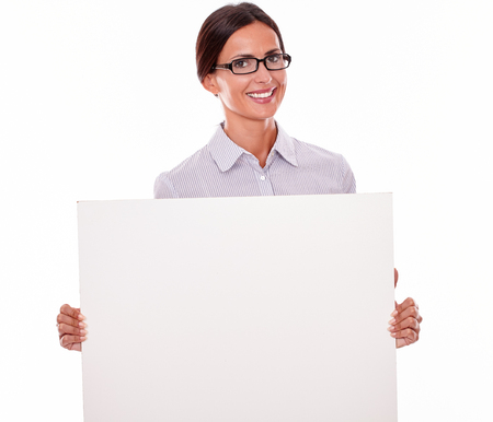 button down shirt: Smiling brunette businesswoman, wearing her hair tied back and a button down shirt, holding a blank placard in front of her on a white background
