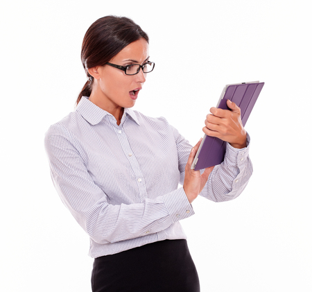 button down shirt: Surprised businesswoman using a tablet while looking at the tablet with her mouth open, wearing her straight hair back and a button down shirt on a white background