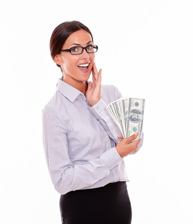 attractiveness: Happy smiling brunette businesswoman looking at camera very satisfied and holding money with one hand on her chin wearing her straight hair back in a button down shirt on a white background