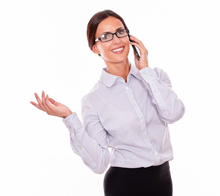 hair back: Happy businesswoman speaking on her cell phone with a toothy smile while looking at the camera with a happy gesture while wearing her straight hair back and a button down shirt, isolated