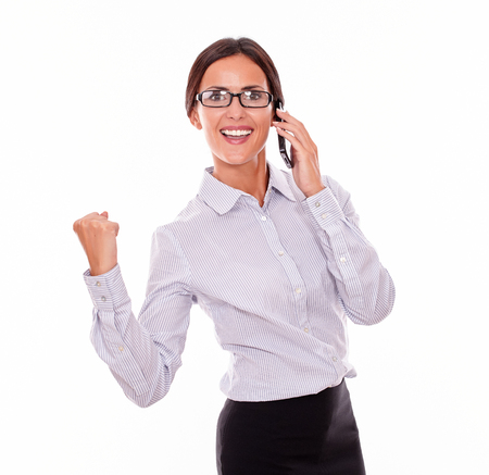 back straight: Celebrating businesswoman speaking on cell phone while looking at camera and making a gesture of victory with one hand an wearing her straight hair back and a button down shirt on a white background Stock Photo