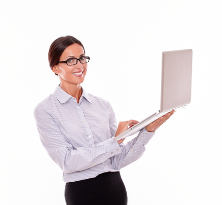 button down shirt: Smiling brunette businesswoman holding a laptop with a toothy smile while looking at the camera and wearing her straight hair back with a button down shirt on a white background