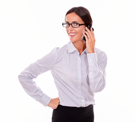 button down shirt: Smiling businesswoman calling on her cell phone while looking at camera with a toothy smile and one hand on her hip while wearing her straight hair back and a button down shirt on a white background