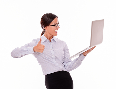 button down shirt: Smiling brunette businesswoman looking at laptop very happy while making a thumb up gesture with one hand and wearing her straight hair back in a button down shirt from waist up on a white background Stock Photo