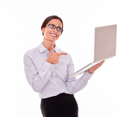 button down shirt: Excited brunette businesswoman looking at a laptop very satisfied while pointing at the laptop and wearing her straight hair back with a button down shirt on a white background
