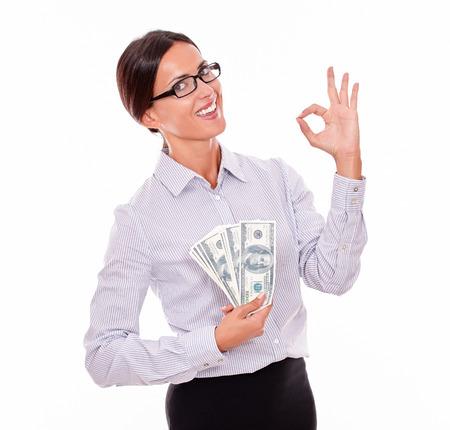 cintura perfecta: Feliz sonriente morena de negocios la celebración de dinero y hace una muestra perfecta con una mano mientras llevaba su cabello hacia atrás y un botón de camisa de cintura para arriba sobre un fondo blanco