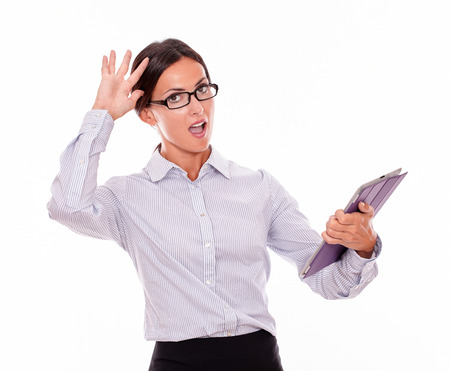 button down shirt: Excited businesswoman with a tablet looking at the camera while looking impressed and wearing her straight hair back with a button down shirt holding one hand on her head on a white background Stock Photo