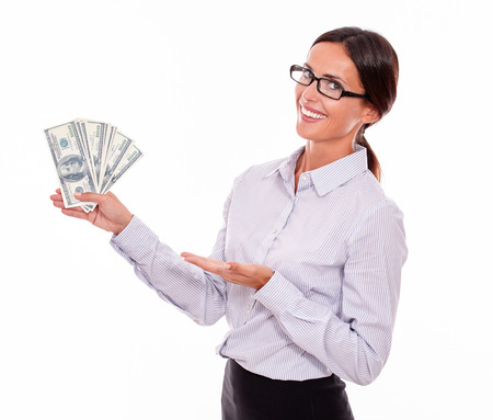 waist up: Happy smiling brunette businesswoman showing money and making a gesture with one hand while wearing her straight hair back and a button down shirt from the waist up on a white background