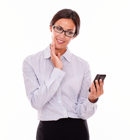 button down shirt: Smiling businesswoman reading a message on her cell phone with one hand on her chin and looking happy wearing her straight hair back and a button down shirt on a white background