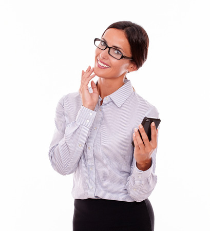 Happy businesswoman holding her cell phone and looking at the camera while making an excited gesture with one hand wearing her straight hair back and a button down shirt on a white background