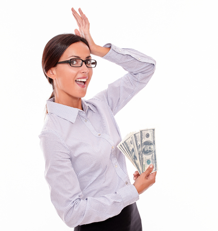 hair back: Surprised brunette businesswoman showing money and holding with a satisfied gesture of her hand to her head while wearing her straight hair back in a button down shirt on a white background