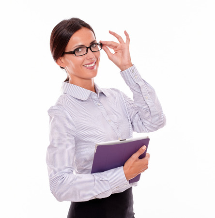 back straight: Smiling businesswoman carrying a tablet while looking at the camera, wearing her straight hair back and touching her glasses with one hand on a white background Stock Photo