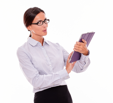 waist down: Thinking businesswoman using a tablet while looking at the camera, wondering, wearing her straight hair back and a button down shirt from the waist up on a white background