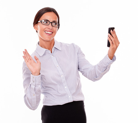 button down shirt: Happy businesswoman taking selfies with her cell phone with a satisfied gesture while wearing her straight hair back and a button down shirt on a white background