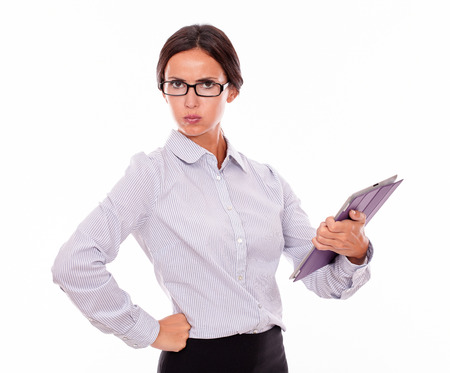 unsatisfied: Disappointed businesswoman with a tablet, looking at the camera very unsatisfied while wearing her straight hair back and a button down shirt with one fist on her hip on a white background Stock Photo