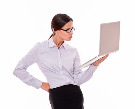 unsatisfied: Unsatisfied brunette businesswoman looking at a laptop very disappointed while wearing her straight hair back and a button down shirt with one hand on her hip on a white background