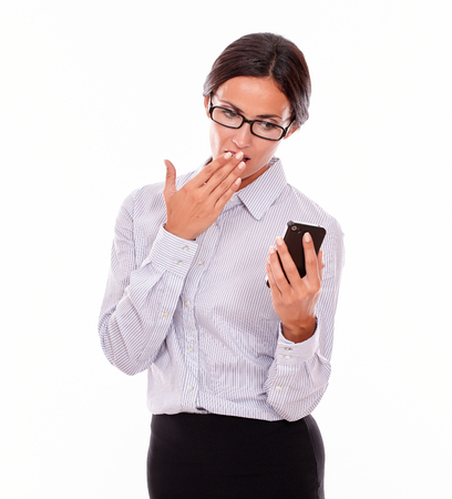 hair back: Shocked businesswoman looking at her cell phone making a surprised gesture with one hand to her mouth while wearing her straight hair back and a button down shirt on a white background