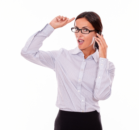 button down shirt: Planning businesswoman speaking on cell phone while looking at camera and making a gesture with one hand while wearing her straight hair back and a button down shirt on a white background Stock Photo
