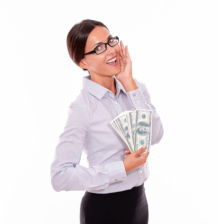 Excited brunette businesswoman holding money with an impressed gesture of her hand to her face while wearing her straight hair back and a button down shirt from the waist up on a white background Stock Photo