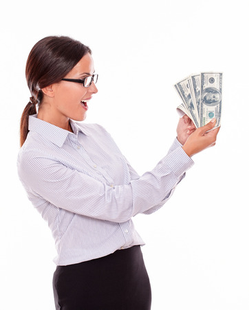 waist down: Happy smiling brunette businesswoman looking at money very impressed while wearing her straight hair back and a button down shirt from the waist up on a white background