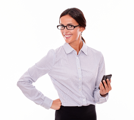button down shirt: Satisfied businesswoman with a cell phone looking at camera with a toothy smile and one hand on her hip while wearing her straight hair back and a button down shirt on a white background