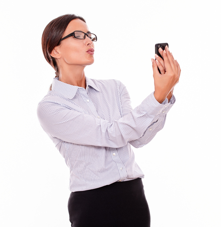 hair back: Happy businesswoman taking selfies with her cell phone and blowing a kiss in a satisfied gesture while wearing her straight hair back and a button down shirt on a white background