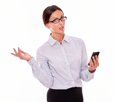 attractiveness: Surprised businesswoman with a cell phone looking at camera with her mouth open and making a gesture with one hand while wearing her straight hair back and a button down shirt on a white background