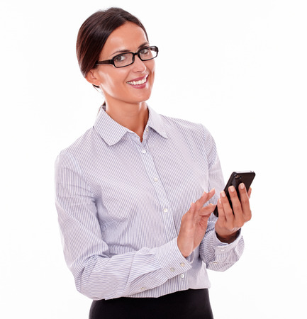hair back: Smiling businesswoman with a cell phone looking at the camera smiling while wearing her straight hair back and a button down shirt on a white background Stock Photo