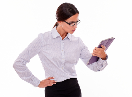 unsatisfied: Stressed businesswoman using a tablet while looking unsatisfied at the tablet and wearing her straight hair back and a button down shirt with one hand on her hip on a white background