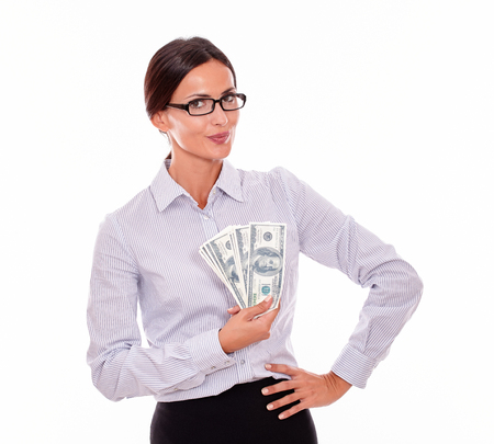 waist down: Happy brunette businesswoman holding money with a satisfied gesture and one hand to on her hip while wearing her straight hair back and a button down shirt from the waist up on a white background Stock Photo