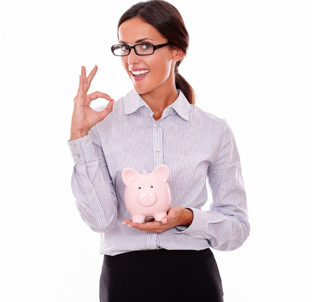 button down shirt: Smiling businesswoman holding pink porcelain piggy bank smiling and looking at the camera while wearing her hair back and a button down shirt with a perfect sign on a white background