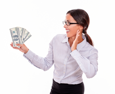 impressed: Impressed brunette businesswoman holding dollar bills with an excited gesture of one hand and smiling while looking at money in a button down shirt and her hair tied back on a white background Stock Photo