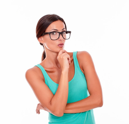 hair back: Planning brunette woman with green tank top looking at the camera with a reflective gesture of a hand on her chin while contemplating and wearing her long hair back on a white background