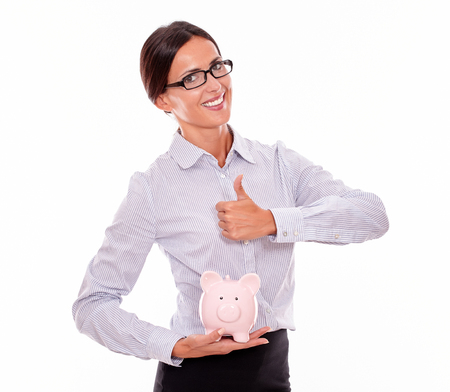 hair back: Businesswoman holding pink porcelain piggy bank with a very satisfied toothy smile and a thumb up gesture wearing her hair back and a button down shirt while looking at camera on a white background