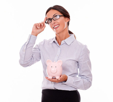 button down shirt: Thinking businesswoman holding pink porcelain piggy bank smiling and looking at the sky while wearing her hair back and a button down shirt with a planning gesture of one hand on a white background
