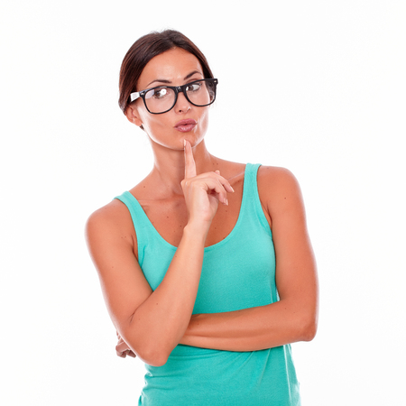 hair back: Planning brunette woman with green tank top looking away with a reflective gesture of a finger on her face while contemplating and wearing her long hair back on a white background Stock Photo